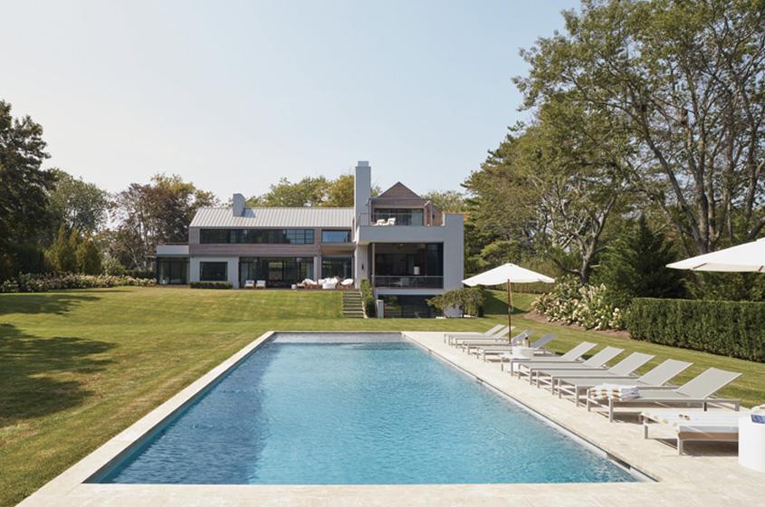 back view new modern Hampton's house, barn shape evokes area. Glass, views of pool